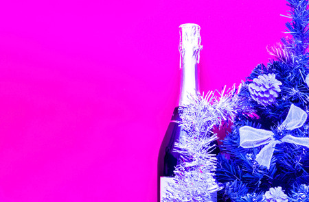 Brilliant Christmas decor.Bottle champagne decorated in festive theme on plastic pink background. Trendy color 2019.Close-up. Copy space