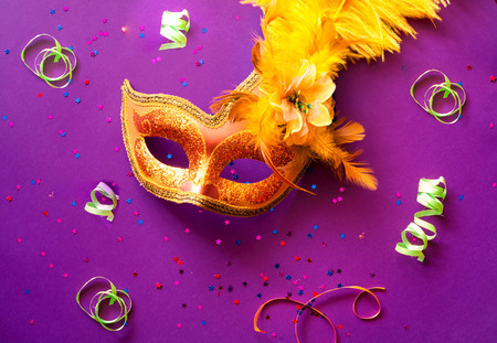 Carnival mask on purple background with sparkles. Festive backdrop for projects.Close-up. Copy space Stock Photo
