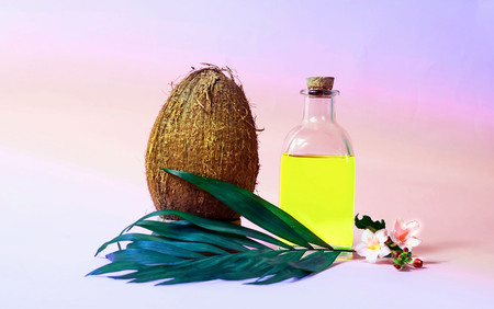 Coconut oil and fresh coconuts on pink  background. Trendy color. Copy space, closeup