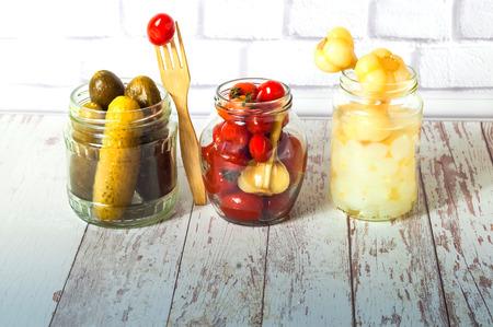 Eingelegte Gurken, kleine Tomaten mit Knoblauch und Zwiebeln im Glas. Fermentiertes Essen. Nahaufnahme. Platz kopieren.