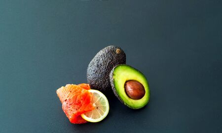 The concept of organic food.Salmon fillet and avocado on dark background. Close-up, copy space