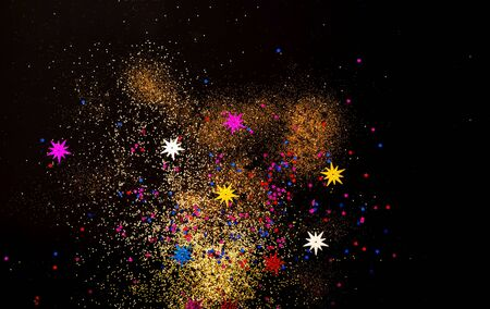 Black background with golden and colored sparkles. Blurred  effect. Concept for festive background or for project.Close-up,copy space