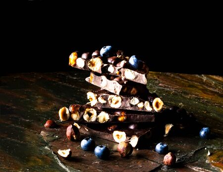 Black chocolate with nuts and blueberries on dark background. Copy space, closeup