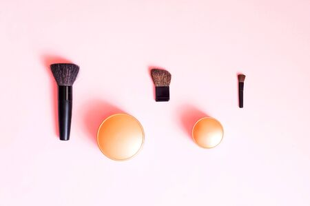 Festive background for decorative cosmetics. Cosmetic brushes and shadows on pastel pink background. Close up, copy space.