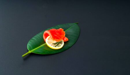 The concept of organic food.Salmon fillet on tropical leaf on dark background. Close-up, copy space