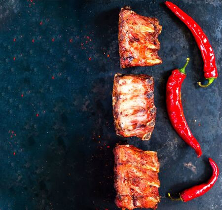 Spicy hot grilled spare ribs from BBQ served with  hot chili pepper on vintage rusty metal background. Copy space, close-up