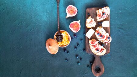 Sandwiches with fresh figs, goat cheese, honey and blueberries on wooden board.Vegetarian food, concept of natural products, choice of healthy food. Copy space, closeup.
