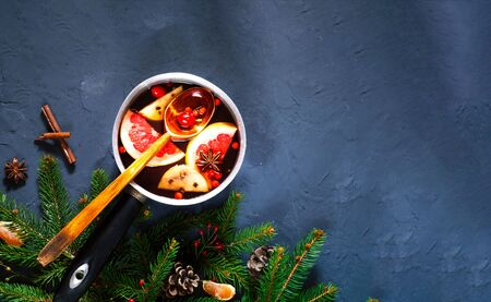 Hot mulled wine with ingredients in authentic ladle on blue concrete background. The concept of celebration and cooking warming drinks.Top view, close up, copy space Фото со стока
