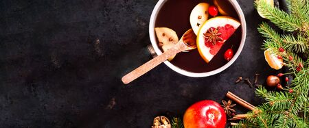 Christmas background. Hot mulled wine with ingredients in authentic ladle on on vintage rusty metal background. The concept of celebration and cooking warming drinks. Top view, close up, copy space