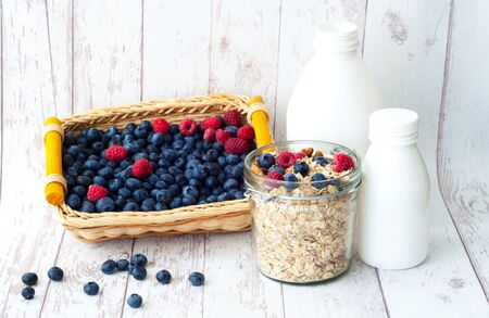 Muesli with blueberries in glass jar on white wooden background. The concept of a healthy breakfast. Stock Photo
