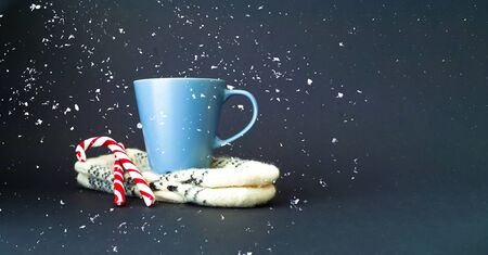 Cup of  tea on knitted mittens. Christmas background. Hyugge style. Close-up, copy space Фото со стока