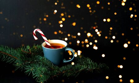 Cup of tea and caramel cane on a texture of pine branches against the background of falling snow. Christmas background. Close-up, copy space