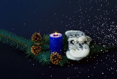 Blue candle and knitted mittens on the texture of pine branches. Christmas background. Hugge style. Close-up, copy space 免版税图像