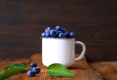 Blueberries in vintage white mug on old wooden boards. Organic food concept. Close-up, copy space.