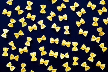 Pattern from Italian pasta farfalle. Food concept. Close-up, copy space Foto de archivo - 129802871