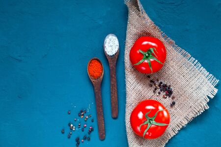 Wooden spoon with spices and red tomatoes on blue background.The concept of healthy eating.Closeup, copy space.