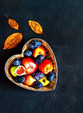 Fruit for the Jewish New Year. Red apples, plums and figs in  straw basket made in the shape of heart on blue background. Copy space