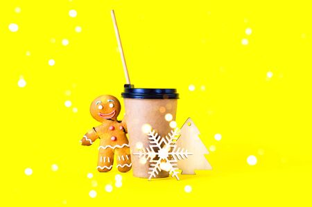 Coffee in paper cup with wooden tube and gingerbread man on trendy yellow background with Christmas decorations.Holiday concept .Close-up. Copy space. 写真素材