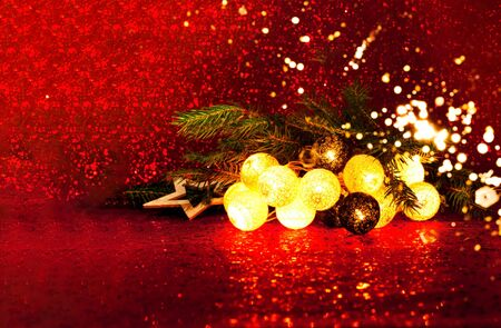 Christmas and New Years decor. Decorative Garland on red background with sparkles. Blurred effect. Close-up, copy space