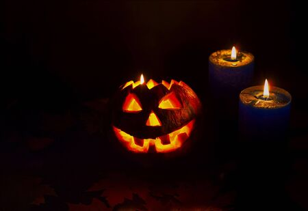 Halloween pumpkin on dark background with candles. Close-up, copy space