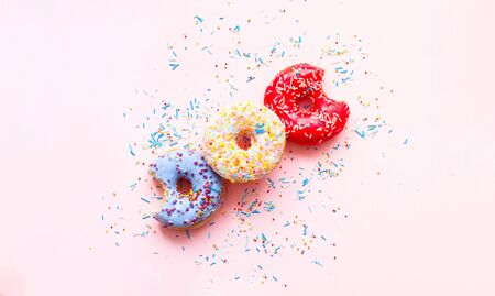 Colored donuts with colorful sprinkles on pink background. Close-up