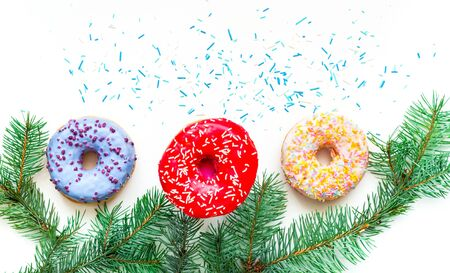 Colored donuts with colorful sprinkles on white background. Christmas and New Year celebration concept. Copy space, close-up