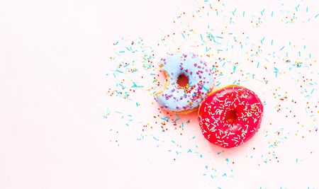 Bitten colored donuts  with colorful sprinkles on pink background. Copy space, close-up Reklamní fotografie