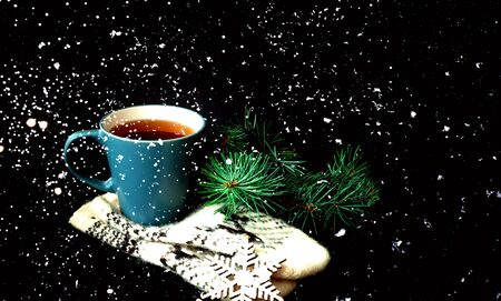 Cup of  tea on knitted mittens. Christmas background. Hygge style. Close-up, copy space Stockfoto