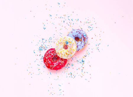 Colored donuts with colorful sprinkles on pink background. Concept colorful breakfast. Copy space, close up Reklamní fotografie