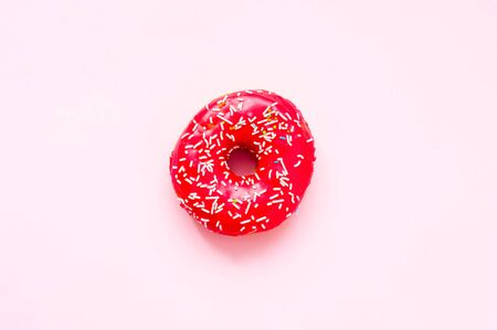 Berry donut with colorful sprinkles on pink background. Concept colorful breakfast. Copy space, close-up