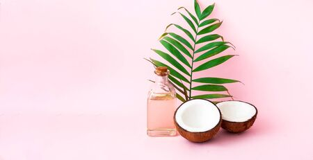 Coconut with coconut oil on pink background. Copy space, close up