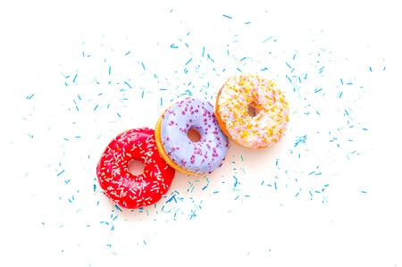 Colored donuts with colorful sprinkles on white background. Copy space, close-up