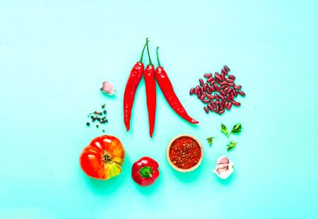 Ingredients for making spicy soup with beans on a green background. Mexican food concept. Close-up, copy space