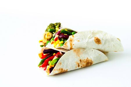 Mexican tortilla with vegetable and mushroom fillings on white background. Healthy eating concept. Budget-friendly menu.Close-up, copy space