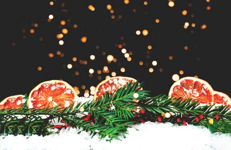 Fir branches with decorations from oranges on texture of snow. Eco decor. Zero waste Christmas concept. Blurred effect. Copy space, close-up
