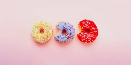 Bitten colored donuts with colorful sprinkles on pink background. Copy space, close-up Standard-Bild