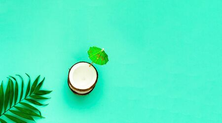 Creative layout of coconuts mit decorative umbrella on green background. Copy space, close-up