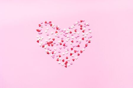 Valentines Day. Heart shape formed of sweet confetti on pink background. Template mock up of greeting card or text design. Close-up