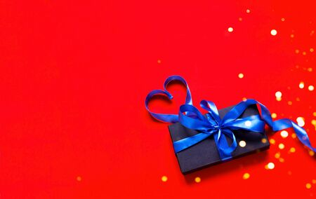 Festive blue ribbon in the shape of heart and black gift box on red background with sparkles. Valentines Day.Template mock up of greeting card or text design. Close-up, copy space Imagens