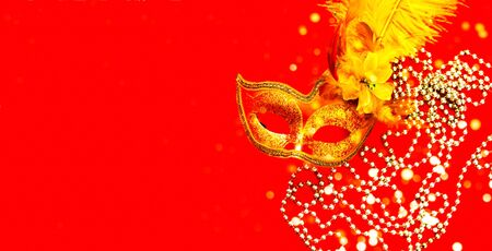 Golden Carnival mask on red background with sparkles and silver beads. Mardi Gras concept. Copy space, close-up Stockfoto