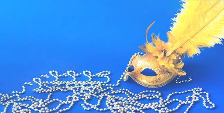 Carnival mask on blue background with silver beads. Mardi Gras concept. Copy space, close-up
