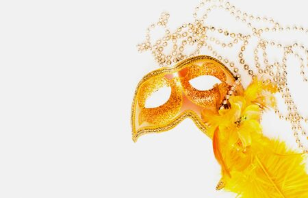 Golden Carnival mask on white background with silver beads. Mardi Gras concept. Copy space, close-up Stock Photo