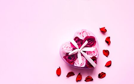 Valentines Day. Heart shape formed of roses flower petals on pink background. Festive concept. Close-up