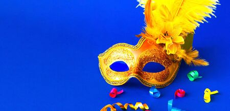 Carnival mask on blue background with sparkles. Mardi gras concept. Copy space, close-up Stock Photo