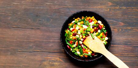 Vegetable mix in authentic pan on wooden background. Mexican food concept. Budget-friendly menu. Close-up, copy space Stock Photo