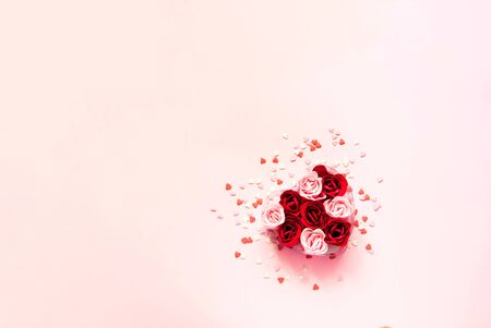 Valentines Day. Heart shape formed of roses flower petals on pink background with sweet confetti. Festive concept. Close-up, copy space