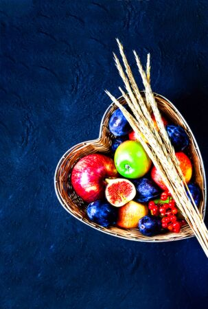 Apples, plums and figs in straw vase made in the form of heart on dark blue background. Copy space, close-up. Stock Photo