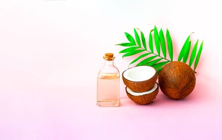 Coconut with coconut oil on pink background. Copy space