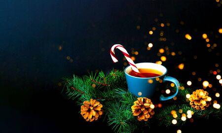 Cup of tea and caramel cane on a texture of pine branches against the background of falling snow. Christmas background. Close-up