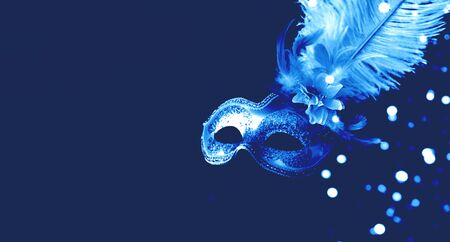 Festive mask with decorative feathers on blue background. Monochrome composition.Mardi Gras concept. Copy space, close-up